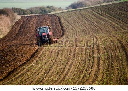 farmer plowing his fields in a beautiful autumnal landscape #1572253588
