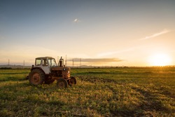 Farmer plowing stubble field with red tractor at sunset.