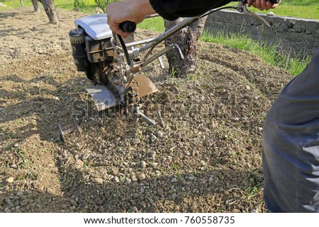 Farmer plowing the earth with motocultivator #760558735