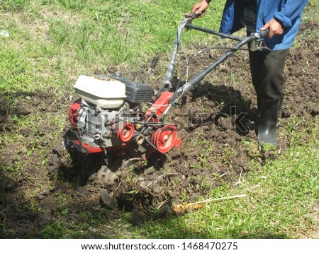 Farmer plowing the land in the garden with a hand tractor cultivator,Soil cultivation.  #1468470275