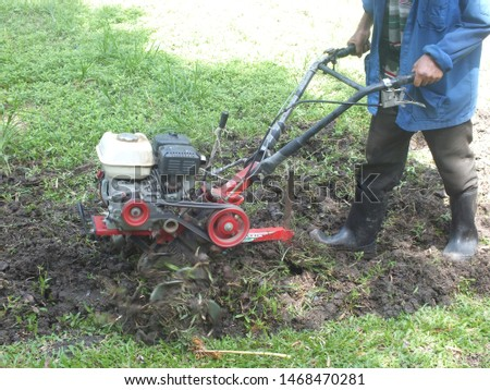 Farmer plowing the land in the garden with a hand tractor cultivator,Soil cultivation.  #1468470281