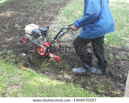 Farmer plowing the land in the garden with a hand tractor cultivator,Soil cultivation.