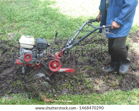 Farmer plowing the land in the garden with a hand tractor cultivator,Soil cultivation.  #1468470290