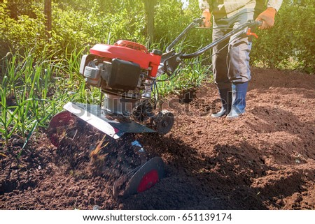 Farmer plows the land with a cultivator, preparing it for planting vegetables, on a sunny day garden #651139174