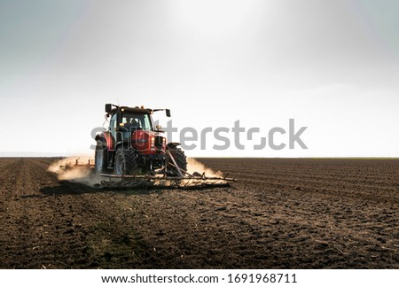 Farmer preparing his field in a tractor ready for spring. Stockfoto ©