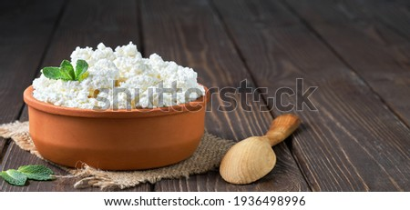 Farmer's cottage cheese in a traditional clay bowl, next to a wooden spoon, a dark wooden background. Close-up, selective focus. Soft curd natural healthy food, wholesome diet food Foto stock ©