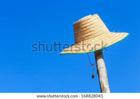 farmer's hat was hanged on bamboo and blue sky in rural ,Thailand