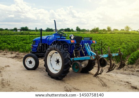 Farmer's tractor with a cultivator plow equipment and field of the Bulgarian pepper plantation. Farming, agriculture. Agricultural universal machinery and equipment, work on the farm. harvesting