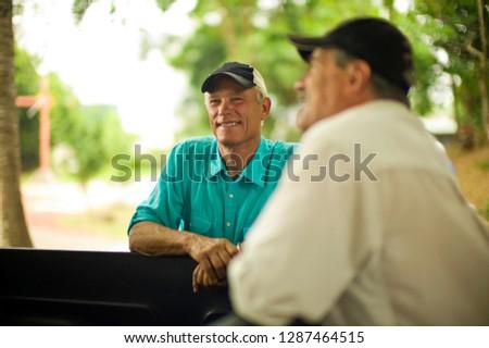 Farmer smiles as he talks with a colleague. #1287464515