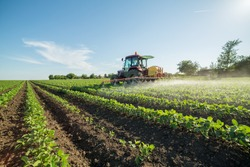 Farmer spraying soybean field with pesticides and herbicides