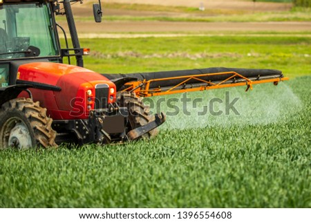 Farmer spraying wheat crops field #1396554608