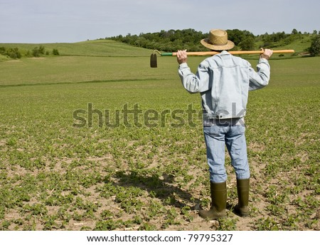 farmer standing in a field with a hoe on his shoulders