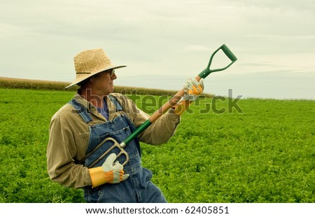 farmer standing in a hay field playing air guitar on his fork
