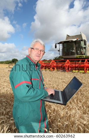 Farmer standing in wheat field with computer