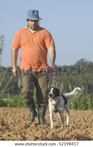 Farmer walking with is dog on the farm