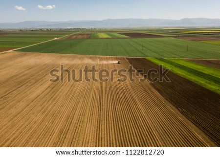 Farmer with a tractor on the agricultural field sowing. tractor working on the agricultural field in spring. aerial view by drone