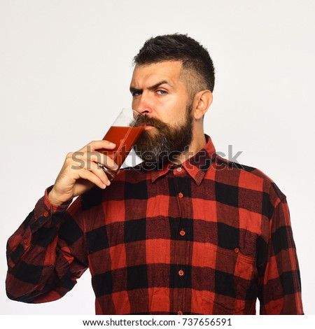 Farmer with strict face holds glass of fresh red juice. Guy shows his harvest. Man with beard drinks tomato juice isolated on white background. Farming and autumn products concept #737656591