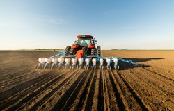 Farmer with tractor seeding - sowing crops at agricultural field. Plants, wheat.