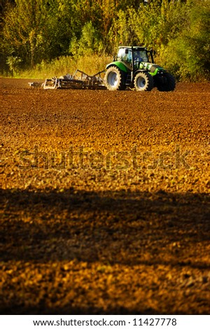 farmer with tractor working on the soil
