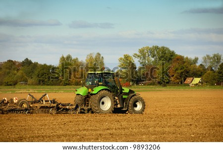farmer with tractor working on the soil - stock photo