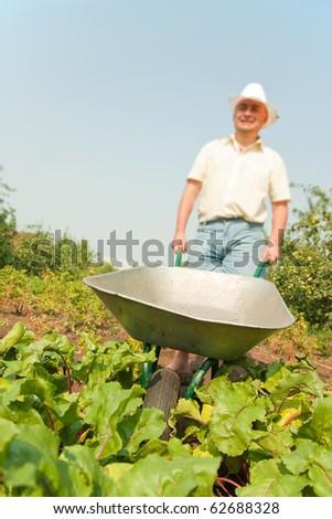 farmer with  wheelbarrow standing in a field . Focus on barrow
