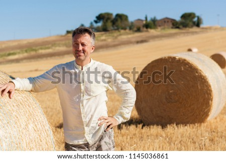 Farmer working on field near bale of wheat. Harvestimg in Tuscany, Italy. Stacks of hay on summer field. Hay and straw bales in the end of summer.