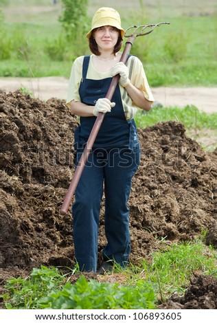 farmer works with manure at farm