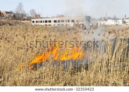 Farmers doing a seasonal burning on the bank of the river - stock photo