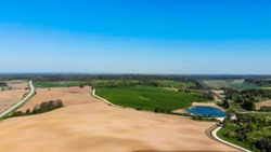 Farmers field. Green farmers field. shot from above, from drone. Field and forest. Beautiful top view of plowed and sown fields. Aerial panorama drone view of typical agricultural landscape.