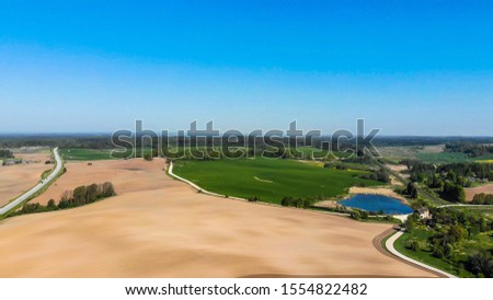 Farmers field. Green farmers field. shot from above, from drone. Field and forest. Beautiful top view of plowed and sown fields. Aerial panorama drone view of typical agricultural landscape. ストックフォト ©