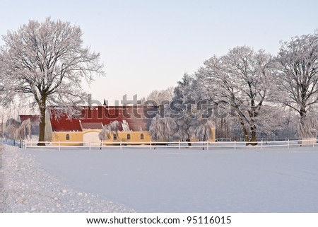 Farmhouse and frosty trees against a blue sky.