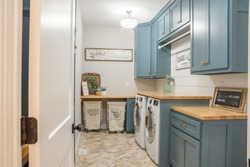 Farmhouse style laundry room, rolling carts, signs, blue cabinets.