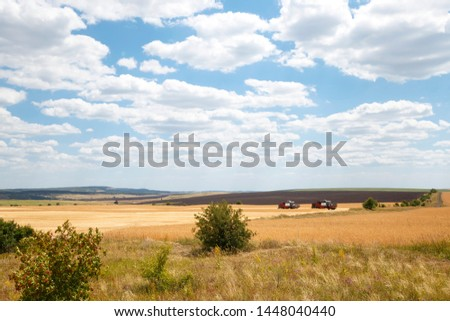 Farming, agriculture. Season of harvesting grain, cereals. Two harvesters working in the field on the harvest of ripe wheat on the background of a beautiful landscape
