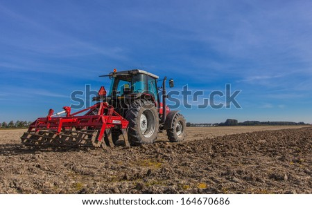 Farming in the Netherlands Tractor with Plough Plowing in a Field under Blue Sky