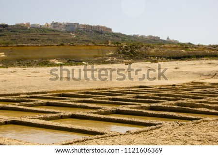 Farming salt in salt fields or salt pans in Gozo with the distinguished view on the little hill in Żebbuġ, Malta directly next to the ocean