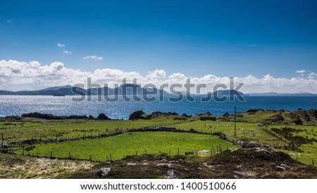 Farmland and glistening ocean waters in Malin Head, Ireland