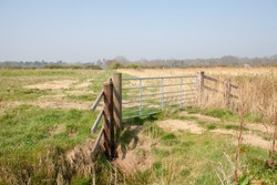 Farmland gate. Country walk along rural Norfolk Broads farm land path UK. Wood and metal gate in the countryside. Access rights for walkers. Scenic landscape view of grass and wheat fields.