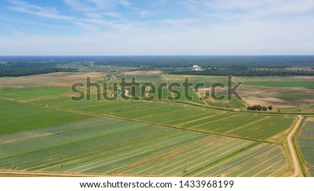 Farmlands with crops and agricultural machinery from above. Countryside with farmland. #1433968199