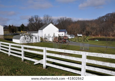 Farmstead and white wooden split rail fence in the country.  There are several buildings on the property and a bright blue sky overhead.