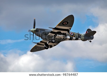 FARNBOROUGH, ENGLAND - JULY 24: A vintage Spitfire fighter plane, in D-Day colour scheme, makes a low flypast for the public at the Farnborough International airshow at Farnborough on July 24, 2010. - stock photo