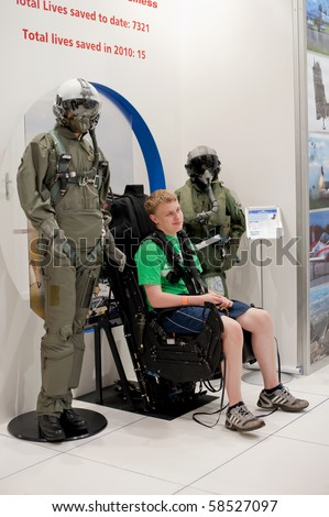FARNBOROUGH, UK - JULY 25: Teenager strapped into the latest Martin-Baker aviation ejection seat at the Farnborough airshow. July 25 2010, Farnborough, Hampshire, UK.