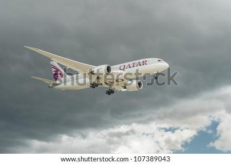FARNBOROUGH, UK - JULY 11: The new Qatar Airways Boeing 787 Dreamliner decending through dark clouds during the international airshow at Farnborough, UK on July 11, 2012