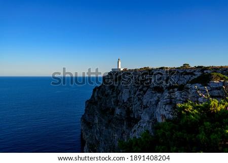 Faro marítimo en acantilado con cielo y mar azul Zdjęcia stock ©