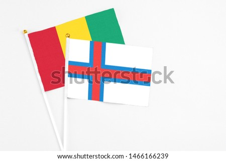 Faroe Islands and Guinea stick flags on white background. High quality fabric, miniature national flag. Peaceful global concept.White floor for copy space. #1466166239