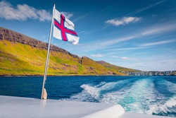 Faroe Islands flag on a motor boat. Picturesque summer seascape of Atlantic ocean. Amazing morning view of Faroe islands, Denmark, Europe. Traveling concept background.