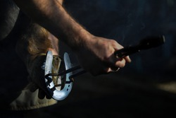 Farrier hot shoeing a horse - adjusting a hot horseshoe to the hoof
