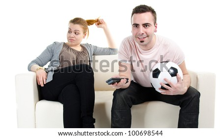 Fascinated man watching football match and bored woman