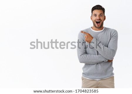 Fascinated, surprised and advertisement concept. Attractive surprised and wondered smiling, excited bearded guy with happy attitude, pointing left and stare impressed camera with awe and excitement Foto stock ©