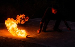Fascinating and dangerous. Man manipulate with burning poi in dark. Burning fuel and energy. Sparks and lights.