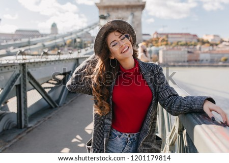 Fascinating girl in knitted red sweater playfully smiling on bridge in sunny day. Outdoor photo of dreamy brunette female model having fun in weekend in Europe.